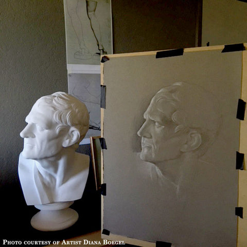 Photo of Cast Drawing of Plaster Cast of Bust of a Man - head turned to his right and a sash on his right shoulder - taped to an easel with the actual cast to its left and drawings on the dark background behind them