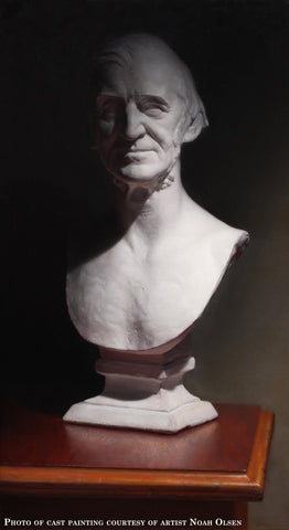 Photo of cast painting of plaster bust of Emerson on a polished wooden table and a background in shadow