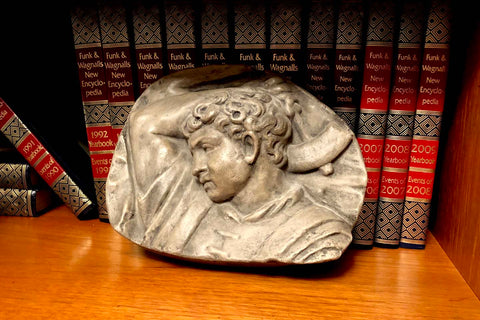 photo of plaster cast sculpture relief of upper body of male with arm raised behind head and holding a hammer leaning against an encyclopedia series in a wooden bookshelf