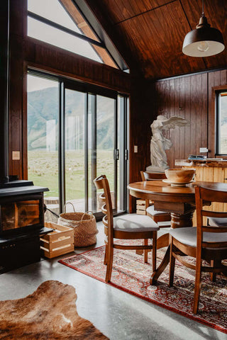 photo of cabin with glass-door wall, table and chairs with hanging lamp above, wood stove, and Victory of Samothrace plaster cast sculpture in the corner on a table