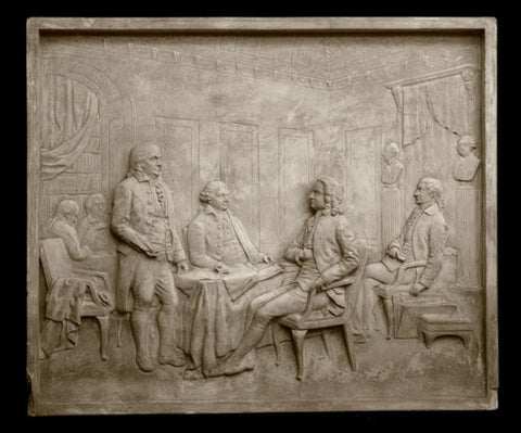 Photo of plaster cast sculpture relief of the signing of the Treaty of Paris depicting several men around a table including Benjamin Franklin and John Adams