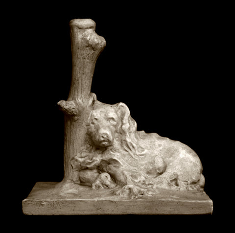 Photo of a Caproni Plaster cast original sculpture of a sleeping dog with it's head against a log on a black background