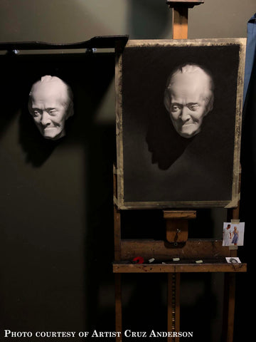 Photo of image of charcoal cast drawing of a plaster cast mask on an easel to the right and original cast hanging on the wall on the left