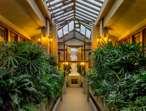 photo of Victory of Samothrace sculpture at the end of a path bordered by green plants in a glass-roofed conservatory with tan colors and warm lighting
