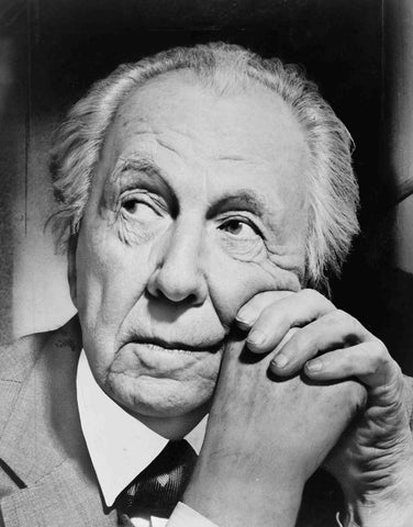 black and white portrait photo of Frank Lloyd Wright with hands clasped at cheek