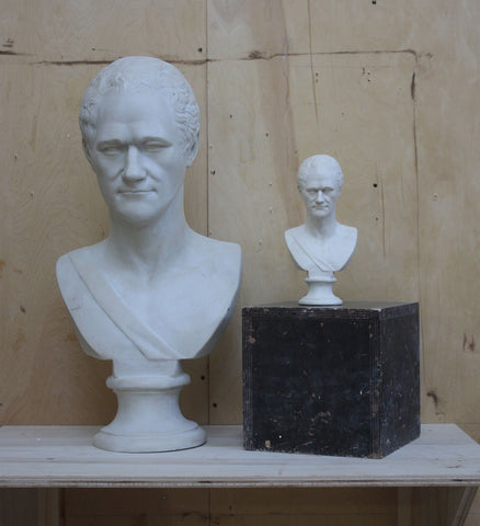photo of large Alexander Hamilton bust beside a small one atop a black box on a wooden shelf