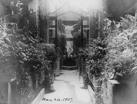 black and white photo of Victory of Samothrace sculpture at the end of a path bordered by plants in a glass-roofed conservatory