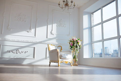 photo of ornate white and gold chair and tall urn with colorful flowers in the middle of a large room with wall window on the right and plaster-work on other visible wall and a crystal chandelier