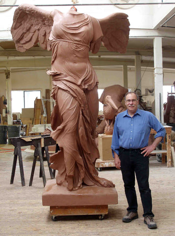 photo of Victory of Samothrace model in red clay beside sculptor Robert Shure in a white-walled and wooden-floored studio with various sculptures, saw horses, and tables