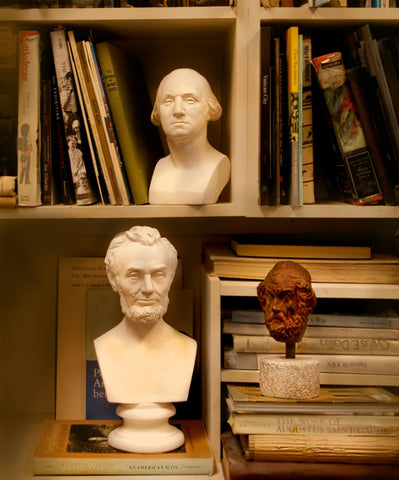 sculpture busts on a table and bookshelf