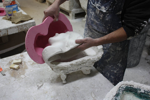 photo of man with blue apron removing plaster cast mask from pink rubber mold and plaster mother mold