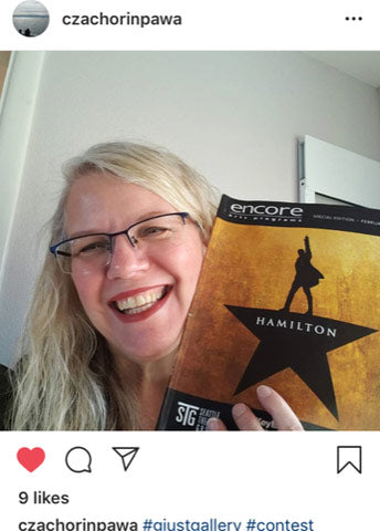 Instagram screenshot of closeup of woman holding Hamilton musical playbill with white wall behind