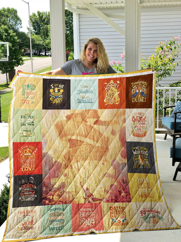 Photo of woman holding up a patchwork quilt on a porch