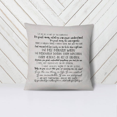 Photo of off-white pillow with rows of lyrics in black leaning against a white wall and on a white bed