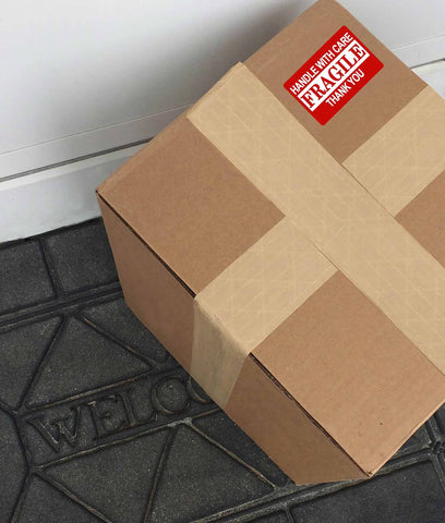 photo of brown package with red fragile sticker on a doorstep with a black welcome mat