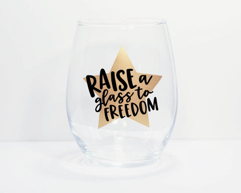 Photo of stemless wine glass with decal of gold star with lyrics in black