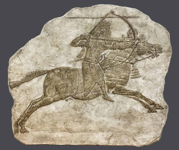 photo of plaster cast of ancient relief of a man on a horse with a gray background