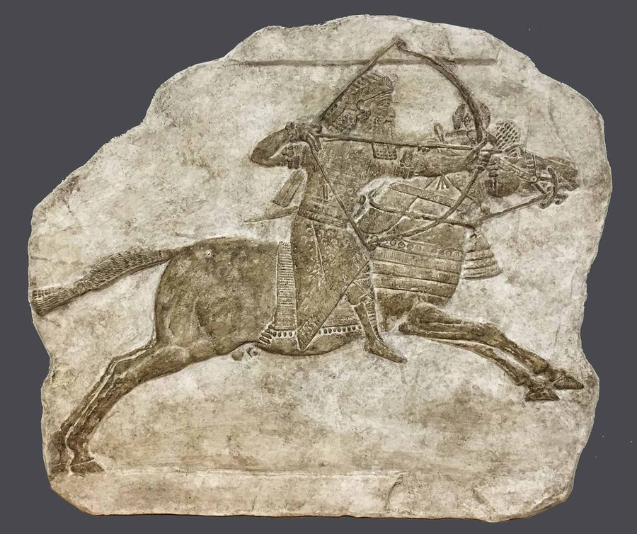 photo of plaster cast relief sculpture of King Ashurbanipal on a horse and aiming an arrow in front of him with a gray background