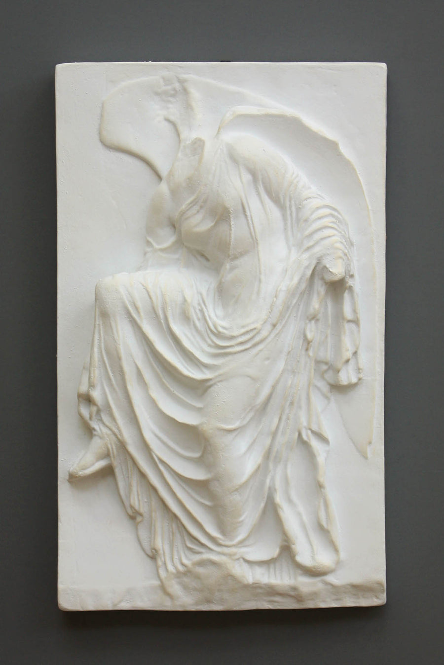 photo of cast of sculpture relief of robed figure, head now missing, reaching for her sandal on a dark gray background