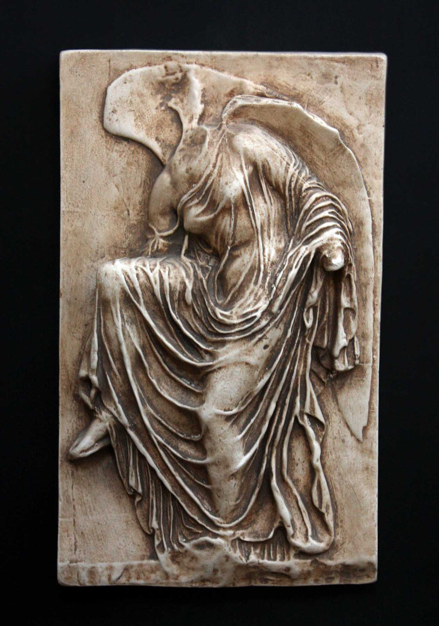 photo of cast of sculpture relief of robed figure, head now missing, reaching for her sandal in a brown patina on a dark gray background