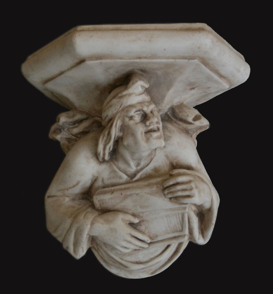 photo with black background of plaster cast sculpture of architectural bracket with a man's upper body who holds a musical instrument