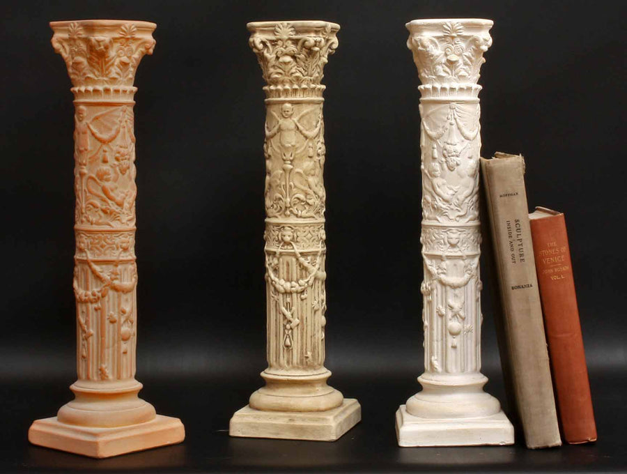 photo of three plaster casts of ornamental candlesticks in terra cotta, tan color, and ivory color and two books propped up against one with black background