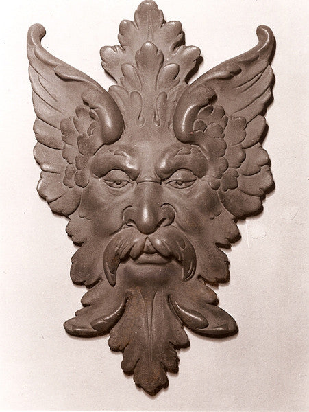 photo of bronze-colored plaster cast sculpture relief of moustached man's face made of leaves with white background
