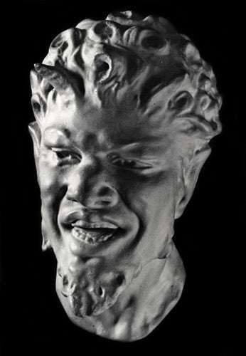 photo with black background of plaster cast sculpture of male faun head with curly hair, horns, beard and open mouth