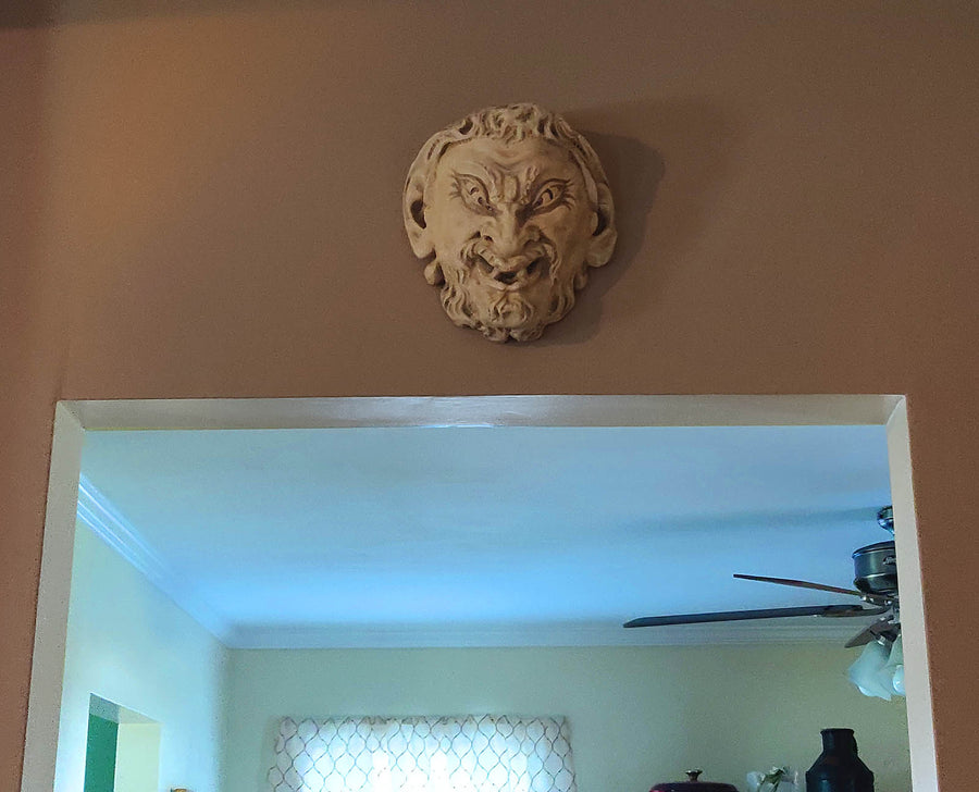 photo of plaster cast sculpture of grotesque faun face, affixed to beige wall above doorway to room with light walls and ceiling fan