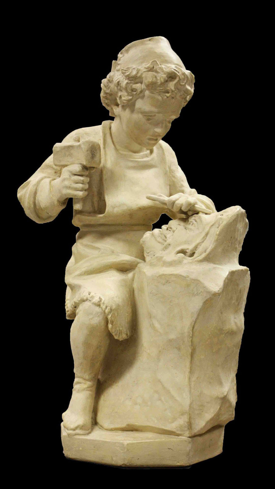 photo with black background of plaster cast of child, namely Michelangelo, on stool with chisel and hammer in hand and sculpting a faun mask from a block of stone