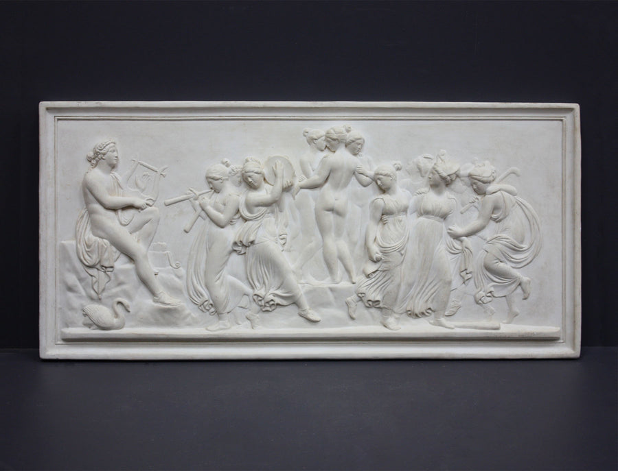 Photo of plaster cast sculpture relief of nude and clothed females (muses) dancing and playing instruments and one male (Apollo) playing a lyre on a dark gray background