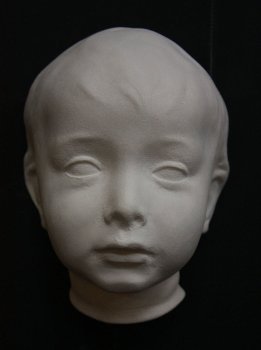 photo with black background of plaster cast sculpture of child's face
