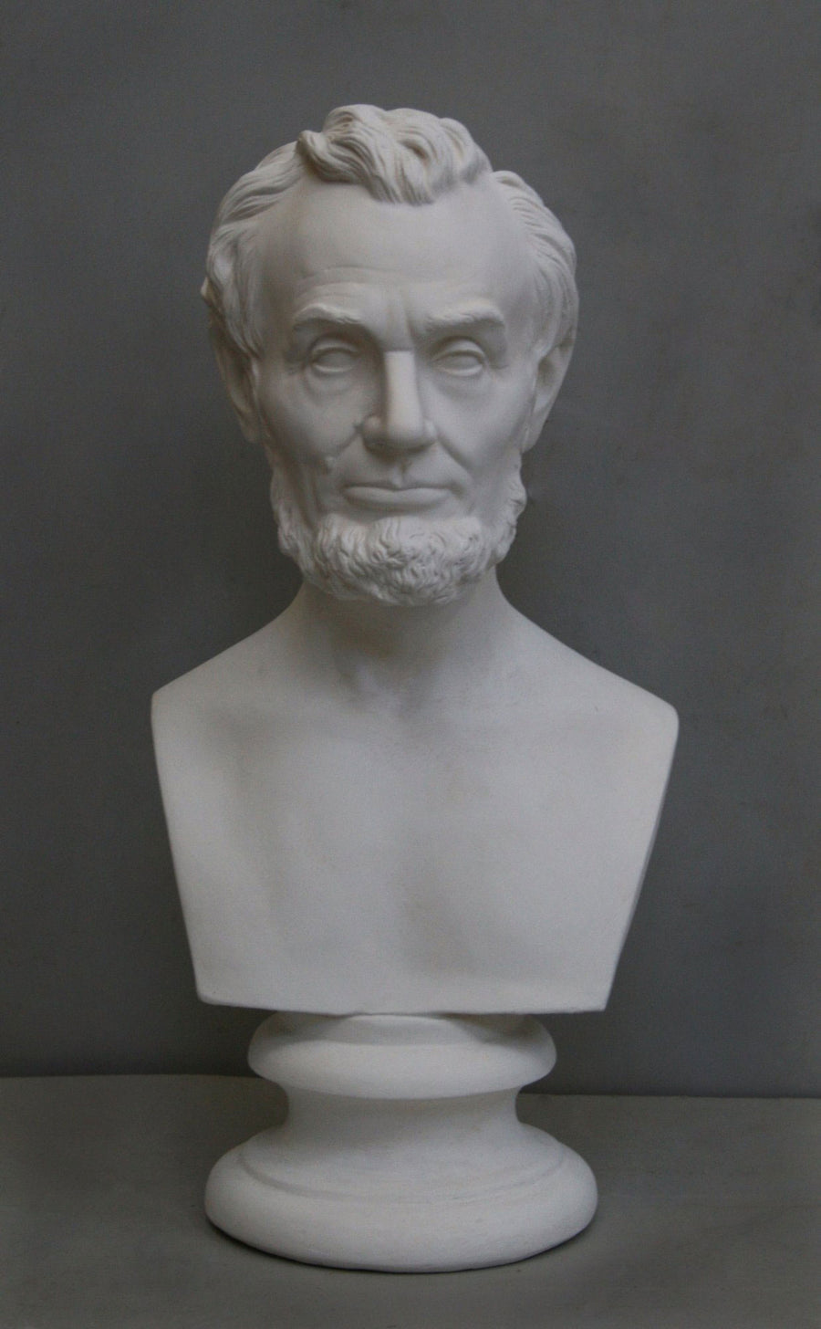 photo with gray background of plaster cast bust sculpture of man with beard, namely Lincoln