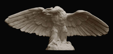 photo on black background of plaster cast sculpture of eagle with wings spread and head turned to its right