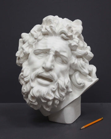 photo with gray background of plaster cast sculpture of male head with curly hair and beard and yellow pencil