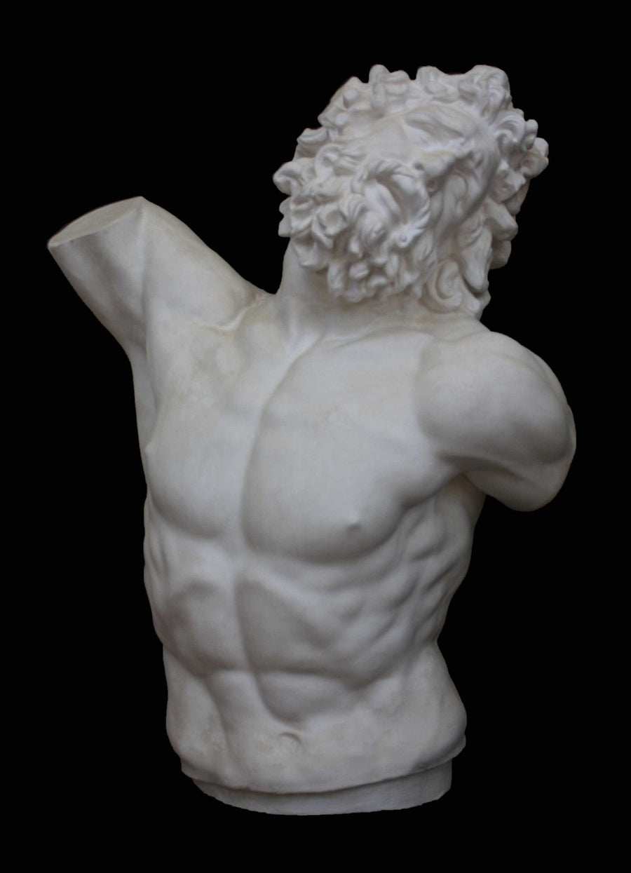 photo with black background of plaster cast sculpture of male torso and head with curly hair and beard, namely Laocoon