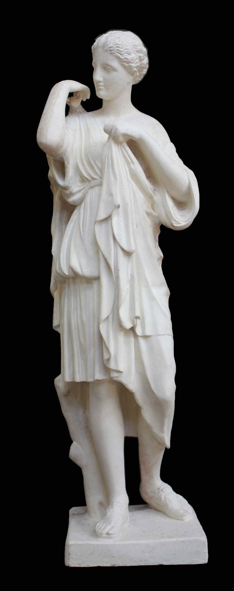 photo with black background of plaster cast of female figure, namely the goddess Diana, with robes about to clasp two pieces together at proper right shoulder