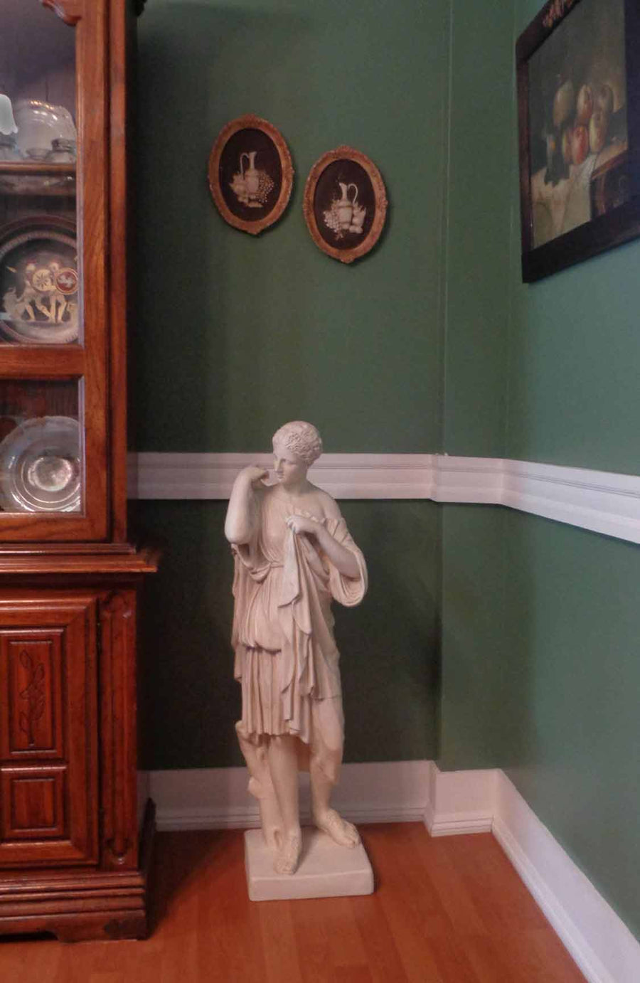 photo of plaster cast of female figure, namely the goddess Diana, with robes on a wood floor in front of a green wall with part of a hutch visible to the left and decorations in hutch and on walls