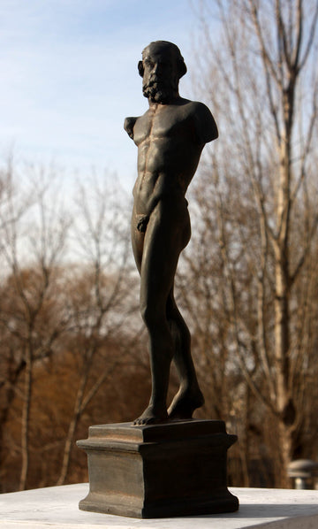 photo of bronze-colored plaster cast sculpture of standing nude satyr figure on square base in front of trees and blue sky