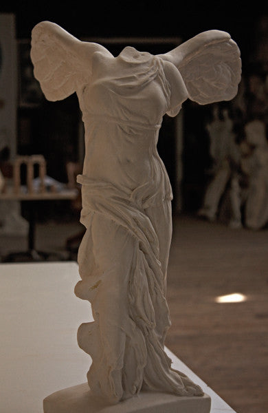 photo of plaster cast sculpture of winged, headless female figure with flowing drapery on a white shelf with wood floor visible and other plaster casts visible in background