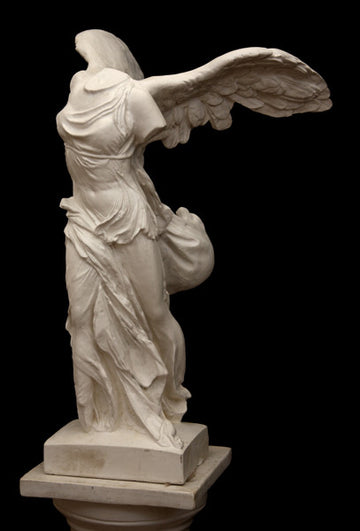 photo of plaster cast sculpture of winged, headless female figure with flowing drapery on top of a Doric-column pedestal on a black background