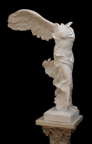 photo of plaster cast sculpture of winged, headless female figure with flowing drapery on top of an ornate, floral pedestal on a black background