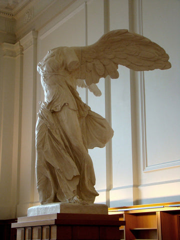 photo of plaster cast sculpture of winged, headless female figure with flowing drapery on top of a ribbed, square, wooden pedestal with white paneled walls behind