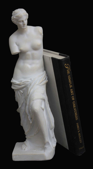 photo with black background of plaster cast sculpture of standing figure of Venus partially nude with a black and white book leaning against it