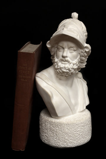 Photo with black background of plaster cast sculpture of male bust with curly hair and beard and helmet and a red book beside it