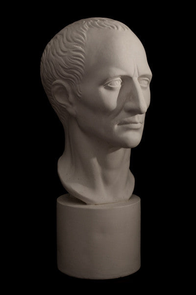 Photo with black background of plaster cast sculpture of man's head on cylindrical base