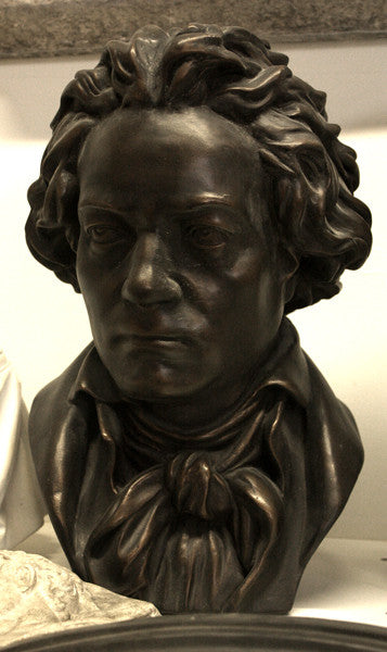 photo of bronze-colored plaster cast sculpture bust of man, namely Beethoven, with neckerchief on light-colored background
