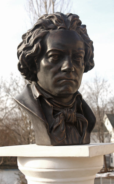 photo of bronze-colored plaster cast sculpture bust of man, namely Beethoven, with neckerchief on pedestal with sky and trees in background