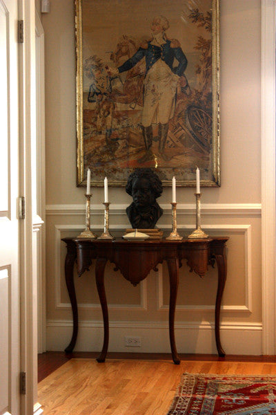 photo of bronze-colored plaster cast sculpture bust of man, namely Beethoven, with neckerchief on dark wood table with candlesticks and portrait painting behind