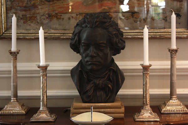photo of bronze-colored plaster cast sculpture bust of man, namely Beethoven, with neckerchief on dark wood table with candlesticks